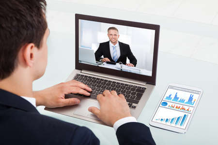 Cropped image of young businessman video conferencing on laptop at desk in office photo