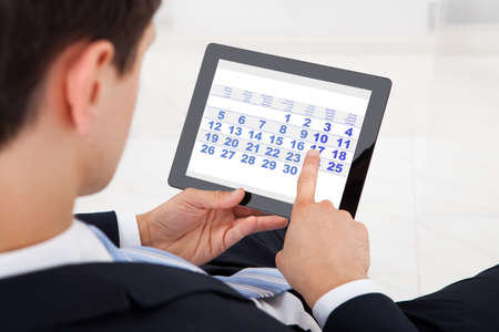 Midsection of businessman using calendar on digital tablet in office photo