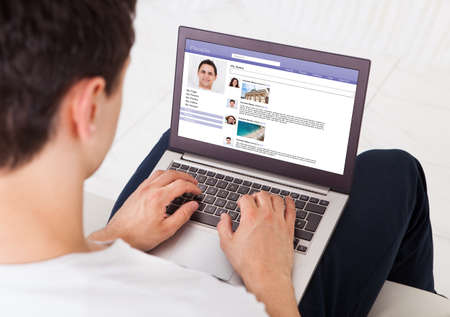 midsection: Midsection of man using social networking site on laptop at home
