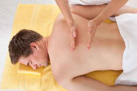 male massage: High angle view of young man receiving back massaging in spa Stock Photo