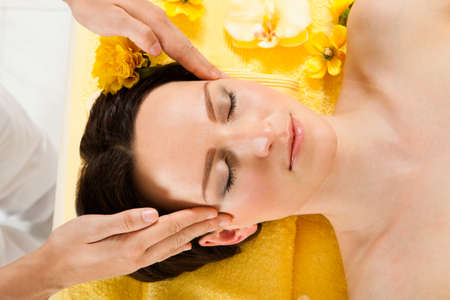 Directly above shot of beautiful woman receiving head massage in spa photo