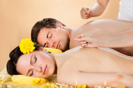 Relaxed young couple receiving acupuncture treatment at beauty spa photo