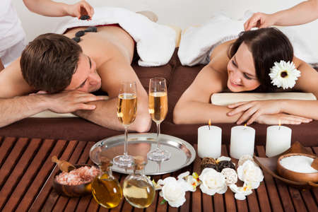 Smiling young couple enjoying hot stone massage at beauty spa photo