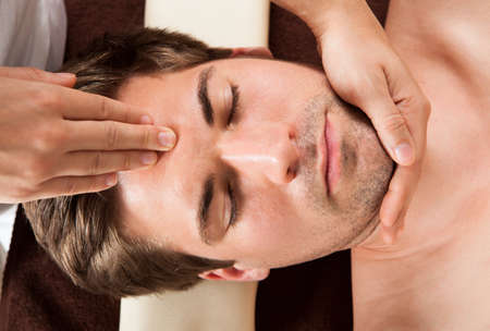 Directly above shot of relaxed young man receiving forehead massage in spa photo