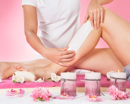 depilaciones: Secci�n media de la pierna femenina del cliente terapeuta encerado en el spa de belleza