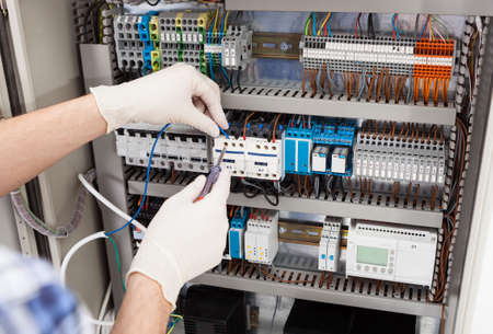 electricity supply: Cropped image of male technician repairing fusebox