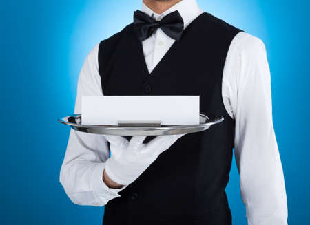 Midsection of young waiter carrying silver tray with blank card over blue background photo