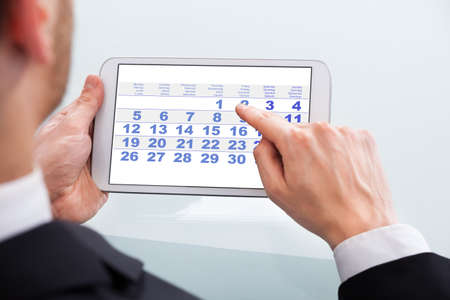 cropped image: Cropped image of businessman touching calendar date on digital tablet in office Stock Photo