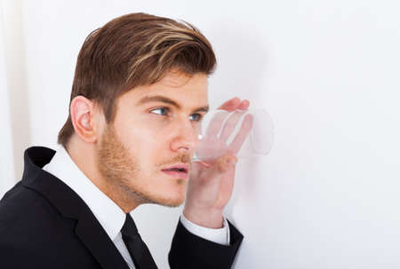 eavesdropping: Young businessman with glass on wall eavesdropping in office Stock Photo