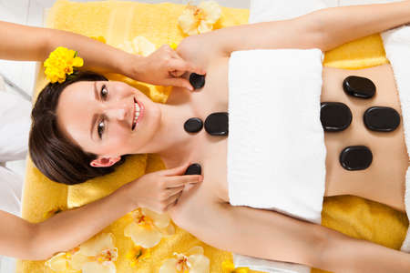 Portrait of beautiful young woman receiving hot stone therapy in spa photo