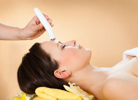 Side view of woman receiving microdermabrasion therapy on forehead at beauty spa photo