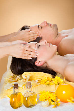 Side view of relaxed young couple receiving head massage at spa photo