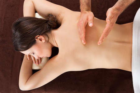 Directly above shot of young woman receiving back massage at beauty spa photo