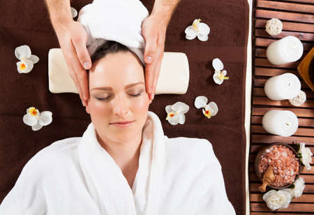 Directly above shot of young woman receiving head massage at beauty spa photo