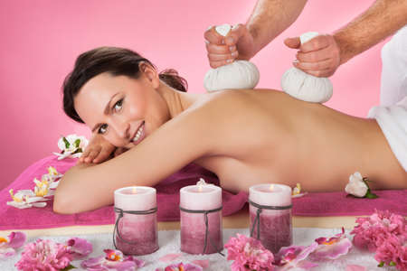 Side view portrait of young woman receiving herbal massage with balls in beauty spa photo