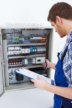 fusebox: Cropped image of male technician holding clipboard while examining fusebox