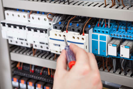 manual test equipment: Cropped image of male electrician examining fusebox with screwdriver