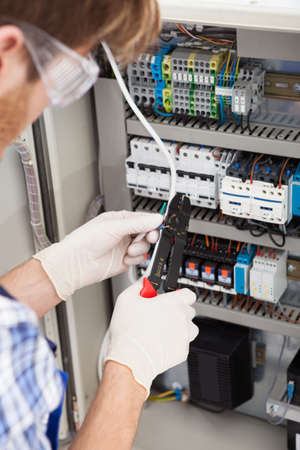 manual test equipment: Cropped image of male electrical engineer repairing fusebox