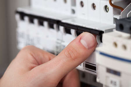fuse box: Cropped image of male technician turning on switch in fusebox