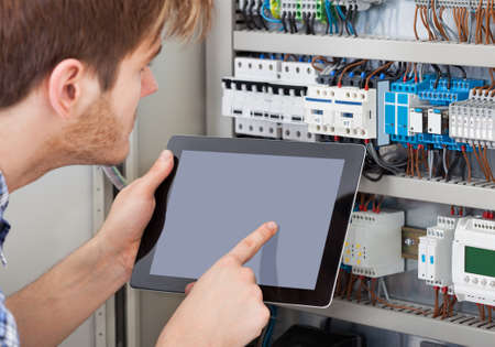 electricista: Vista lateral de t�cnico var�n examinar la caja de fusibles, mientras que la celebraci�n de la tableta