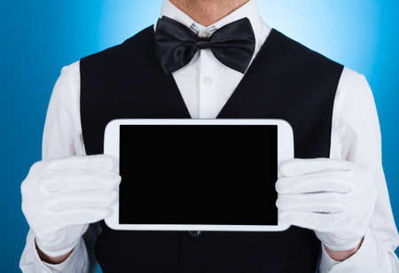 hospitality staff: Midsection of waiter showing digital tablet over blue background