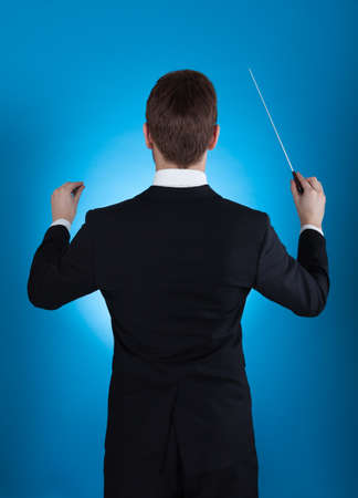 conductor: Rear view of orchestra conductor holding baton against blue background