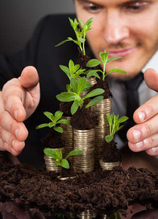 Young businessman protecting coins in saplings representing responsible business against black background photo