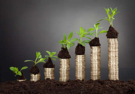 representing: Saplings on stack of coins representing growth against black background Stock Photo