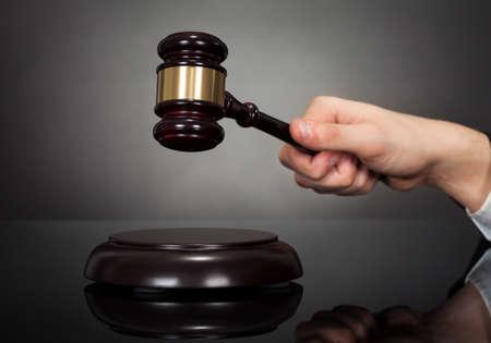 Cropped image of male judge hitting gravel at desk against black background photo