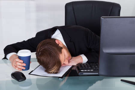 broken contract: Overworked businessman holding disposable coffee cup while resting on contract paper at office desk