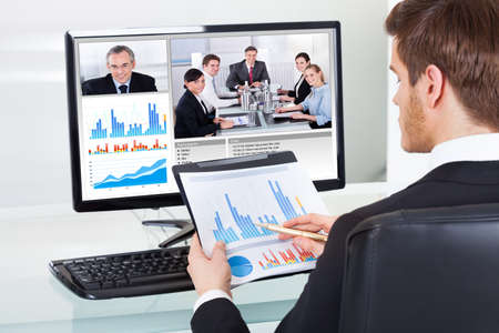 conferencing: Young businessman analyzing graphs while video conferencing with colleagues on computer at office desk