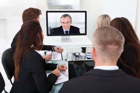 looking at computer screen: Businesspeople attending video conference at desk in office
