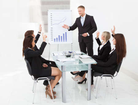 Businesspeople with hands raised answering businessman in meeting at office photo