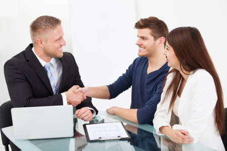 financial advisor: Smiling financial advisor shaking hand with couple at office desk