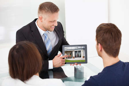 client meeting: Smiling advisor showing house picture to couple on tablet at office desk