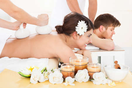 herbal massage ball: Portrait of happy woman receiving massage with herbal compress stamps on back at spa Stock Photo
