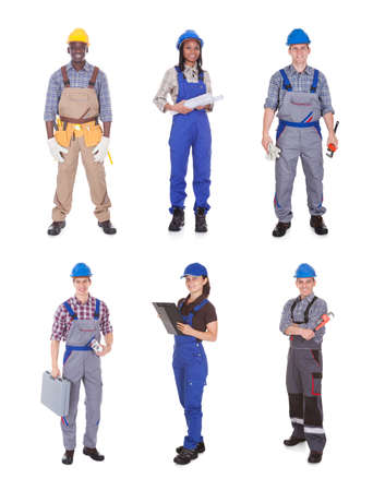 standing against: Full length portrait of confident manual workers standing against white background Stock Photo