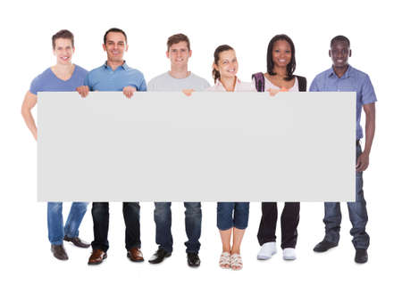 Full length portrait of diverse people in casuals holding blank placard over white background photo