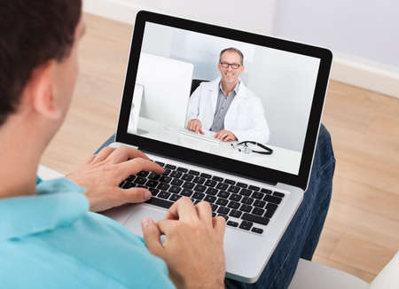 consulting: Man having video chat with doctor on laptop at home Stock Photo