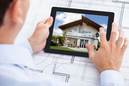 building plan: Cropped image of architect analyzing house on digital tablet over blueprint in office Stock Photo