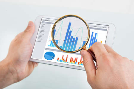 Cropped image of businessman examining graph on digital tablet with magnifying glass at office desk photo