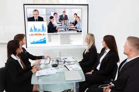 Ondernemers op zoek naar projectiescherm in videoconferentie vergadering op kantoor