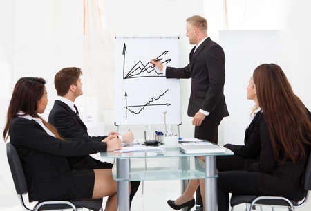 Businessman writing on flipchart while giving presentation to colleagues in office photo