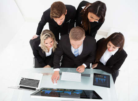 High angle view of businesspeople using desktop PC together at desk in office photo