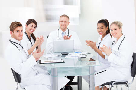Portrait of confident doctors applauding while sitting at desk in clinic photo
