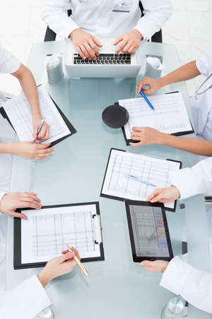 vertical: Cropped image of doctors examining medical reports at desk in clinic Stock Photo