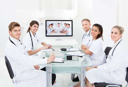 Team of doctors attending video conference at desk in hospital Stock Photo