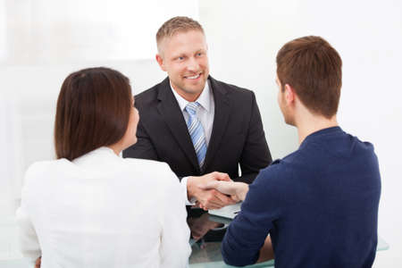 career counseling: Smiling financial advisor shaking hand with young couple at office desk