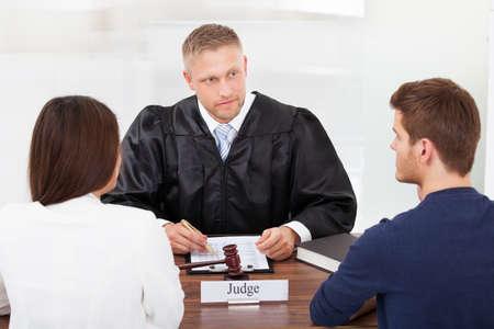 jurado: Vista posterior de la pareja con la escritura de juez en el escritorio en la corte