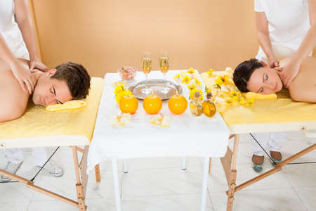 four hands: Relaxed young couple receiving shoulder massage at beauty spa
